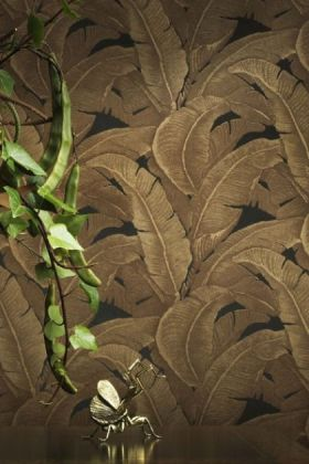 lifestyle image of teide tropical leaves wallpaper - darks - 4 colours available with plant in foreground