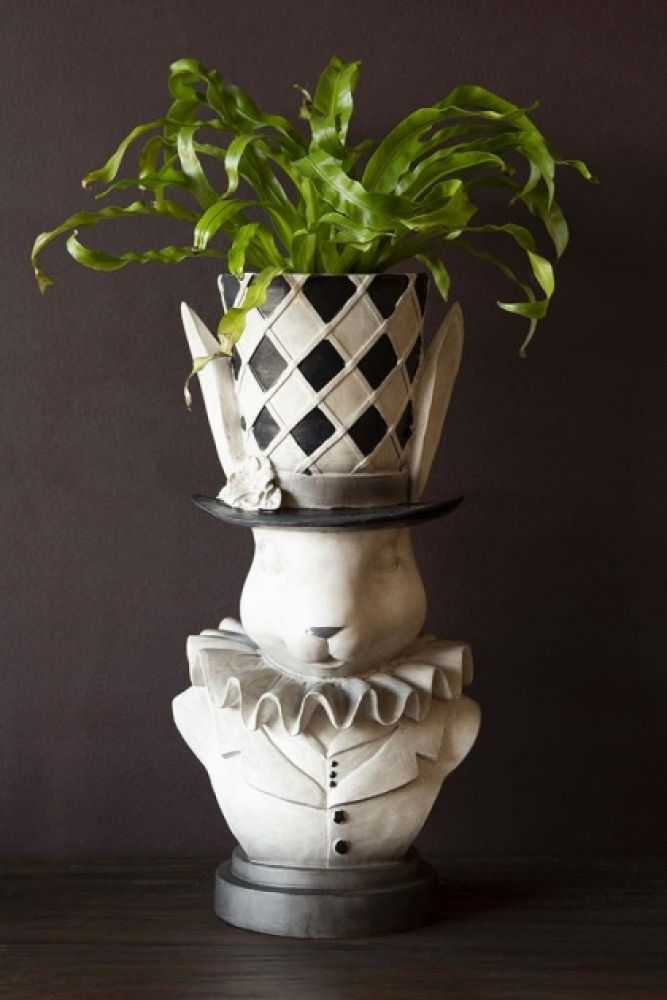 Lifestyle image of the Alice In Wonderland 'Rabbit' Bust Plant Holder with plant inside on dark table and dark wall background