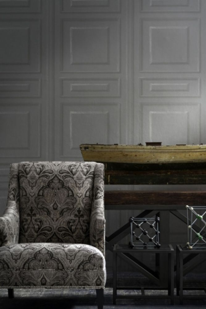 lifestyle image of andrew martin attic collection trianon wallpaper - 5 colours available with patterned armchair and wooden unit behind metal side tables