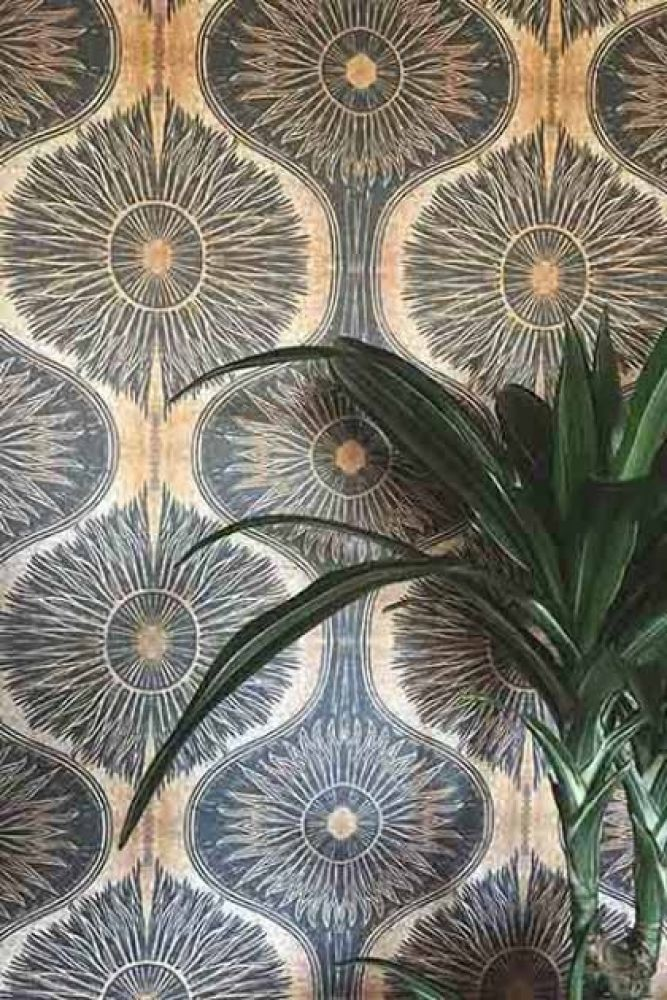 close-up lifestyle image of anna hayman designs gold & black bibana wallpaper with large plant in corner