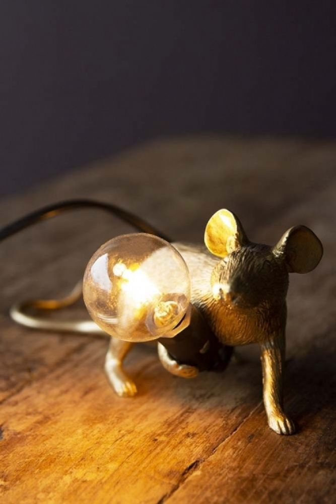 Lifestyle image of Aramis The Crouching Mouseketeer Lamp - Gold lit up on wooden table and dark wall background