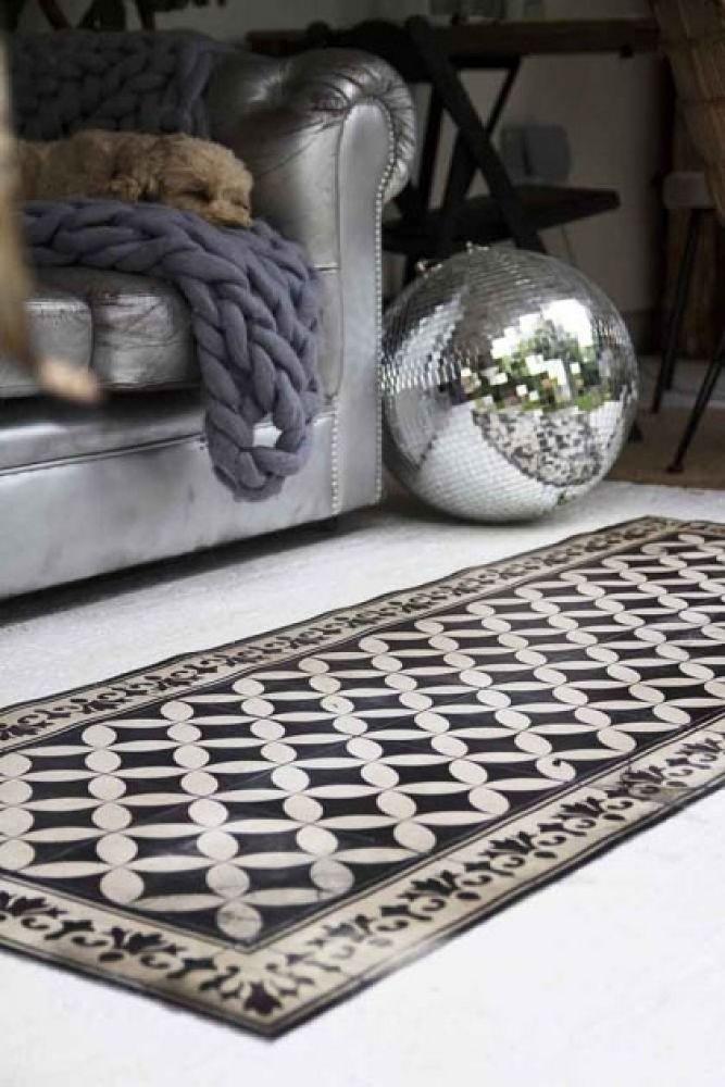lifestyle image of beija vinyl floor runner - sofi antique on floor with disco balls and grey sofa