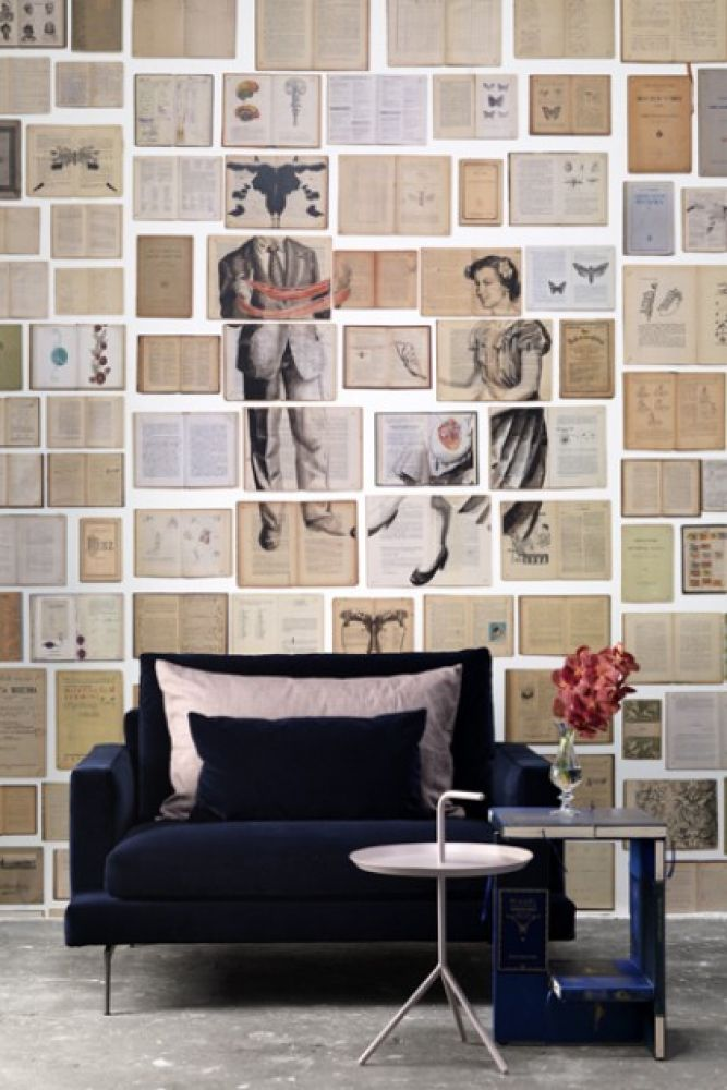 lifestyle image of nlxl biblioteca wallpaper by ekaterina panikanova - mural 4: sewing with black velvet armchair and blue book side table