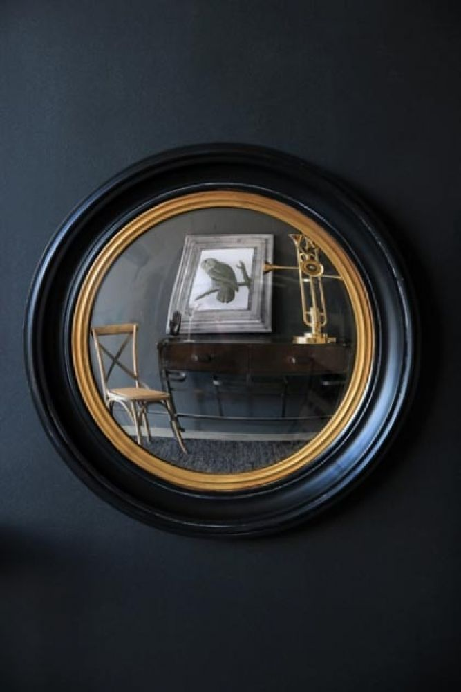 lifestyle image of black and gold framed convex mirror hanging on a dark blue wall hung on dark wall background
