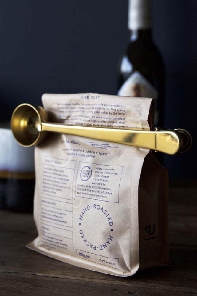 lifestyle image of Brass Finish Coffee Scoop With Clip on bag of coffee beans on wooden table and dark blue wall background