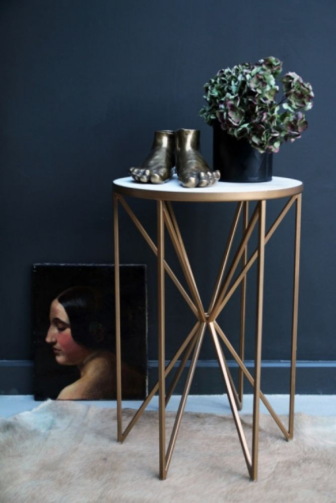 lifestyle image of Brass & White Marble Butterfly Side Table with plant and gold feet ornaments on cowhide and picture on floor