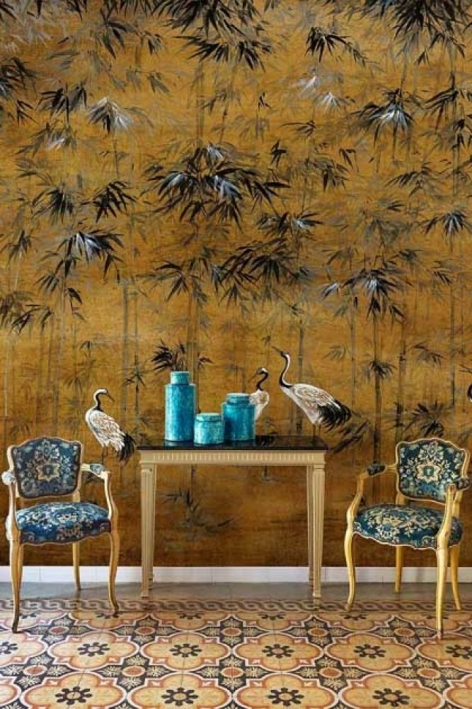 Lifestyle image of the Chinoiserie Wallpaper Mural - Garzas Chai with two patterned chairs and wooden side table with blue vases on top on patterned flooring