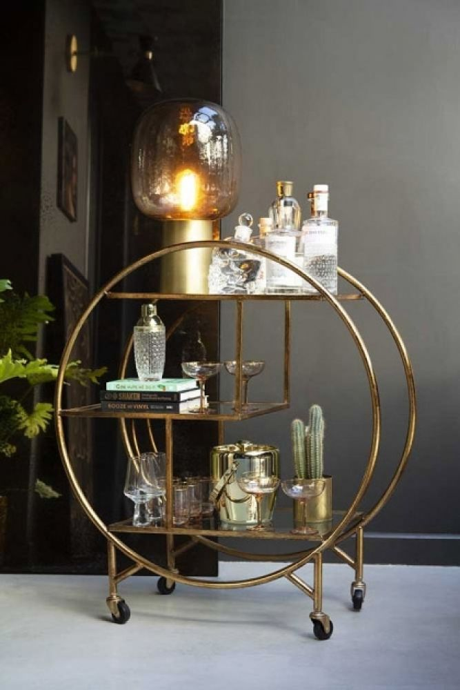 lifestyle image of Circular Art Deco 3-Tier Drinks Trolley filled with bottles and accessories in front of mirror on grey flooring and grey wall background