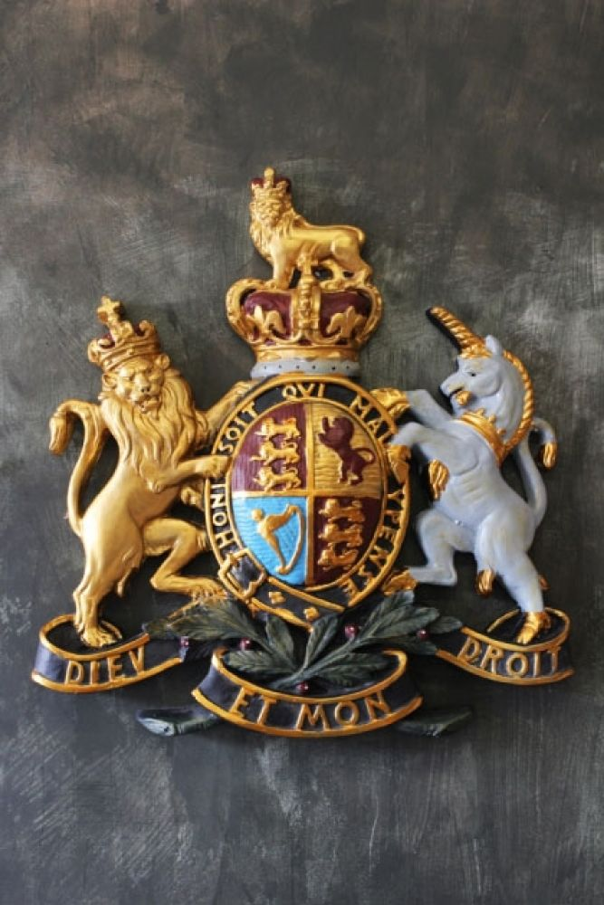 lifestyle image of coat of arms wall plaque on distressed grey wall