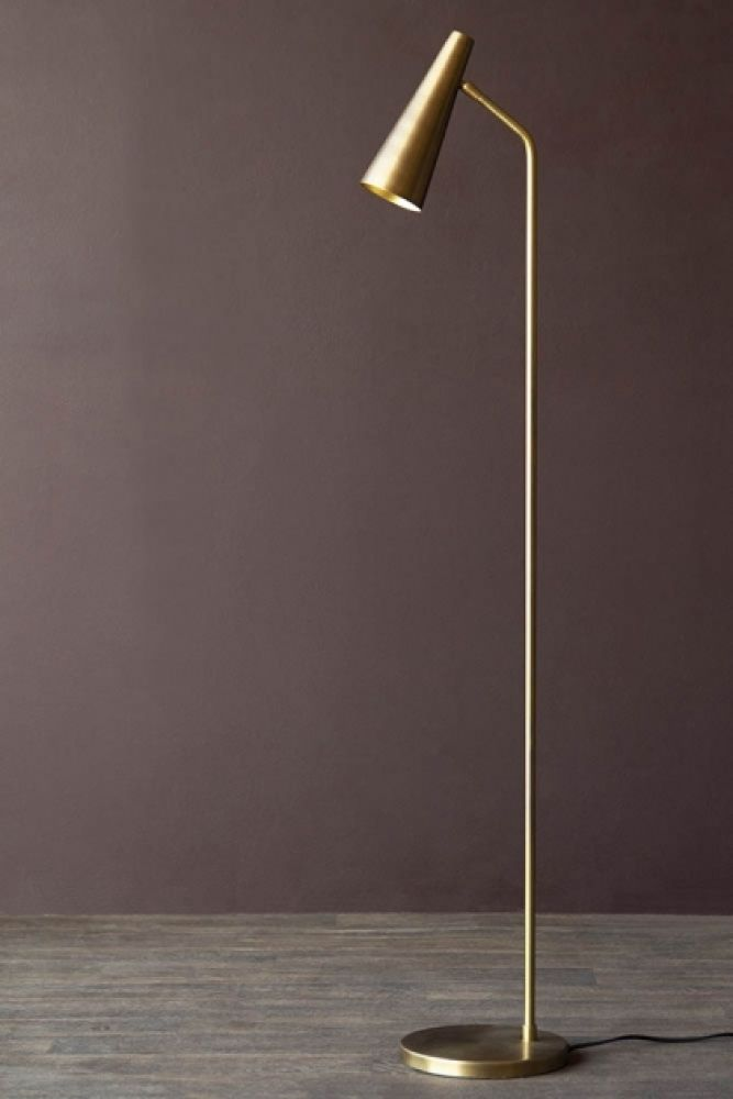 Lifestyle image of the Contemporary Brass Floor Lamp with dark wall background and grey flooring
