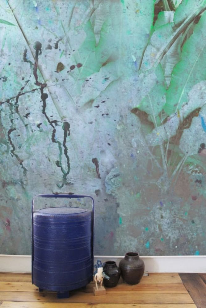 lifestyle image of elli popp wise pond - a frog jumps wallpaper with blue metal barrel and small vases on floor