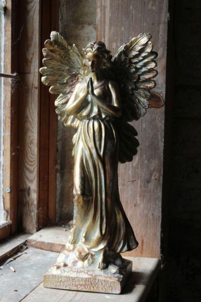 gold finish angel ornament on rustic windowsill lifestyle image