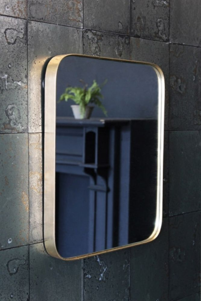lifestyle image of gold framed mirror with black fireplace and plant in reflection on antique mirror wallpaper