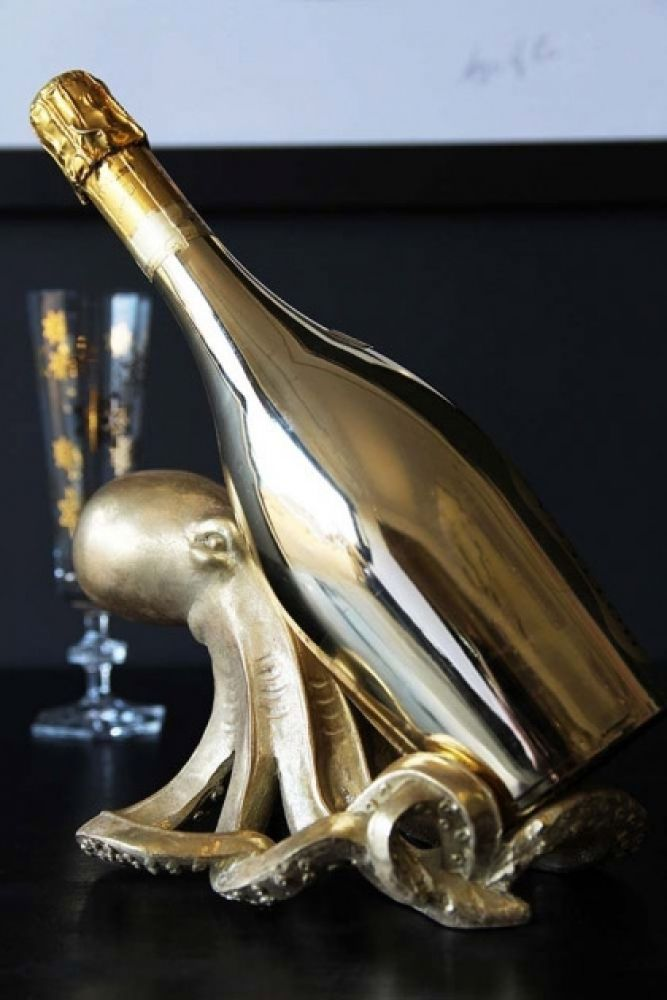 lifestyle image of gold octopus wine bottle holder with gold champagne bottle on black table with Ritzenhoff Champagne Flute - Nerodiseppia in background