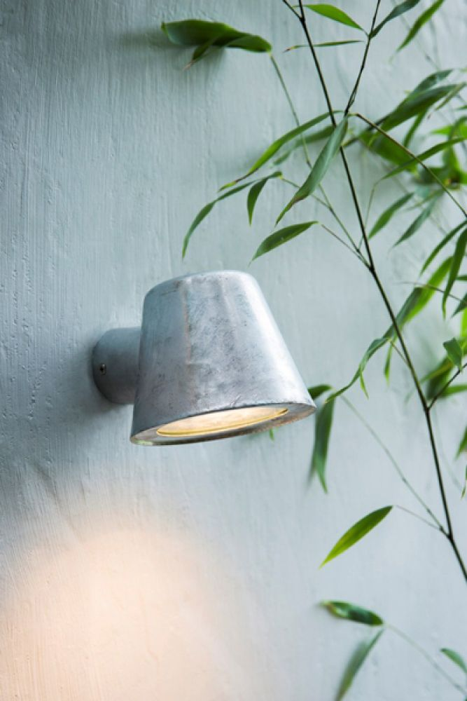 lifestyle image of st ives hot dipped mast wall light lit up with bamboo plant on pale grey wall background