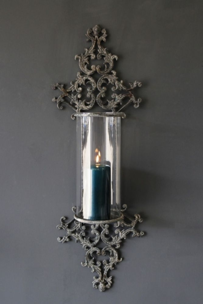 lifestyle image of metal filigran candle wall sconce with blue candle inside on grey wall background