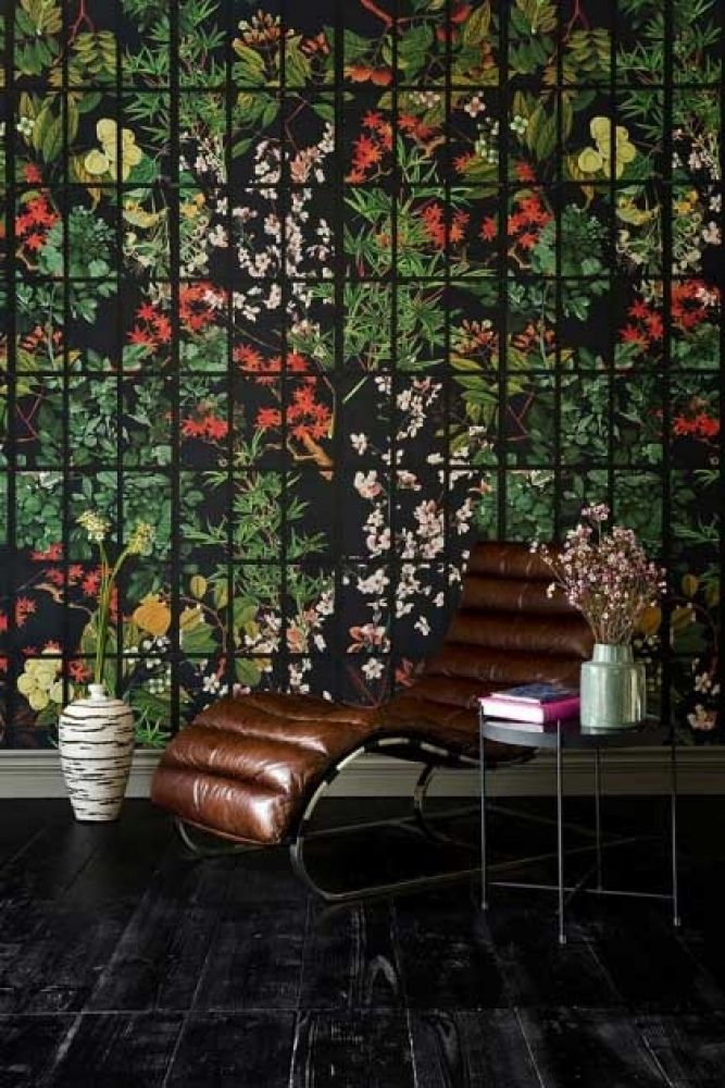 Lifestyle image of Japanese Garden wallpaper in anthracite  with chair and side table in front of it with brown chair and black metal side table with blue vase with pink flowers inside