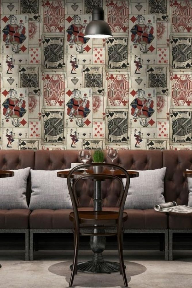 lifestyle image of mind the gap playcards wallpaper with grey sofa with white cushions and wooden chair at small round table