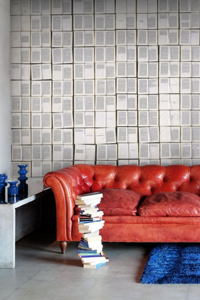 lifestyle image of mr perswall communication  booked, hooked on stories - P130501-8 behind red leather sofa on blue rug and white side table with blue glass vases