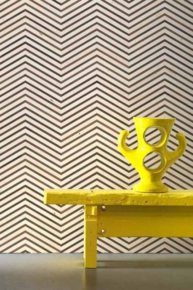 Lifestyle image of NLXL TIM-04 Timber Strips Wallpaper by Piet Hein Eek with bright yellow coffee table and yellow sculpture ornament on top