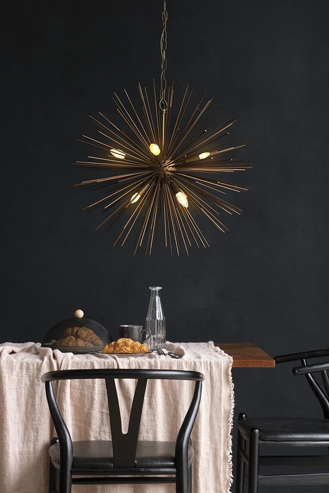 lifestyle image of starburst brass beam pendant lamp over table setting