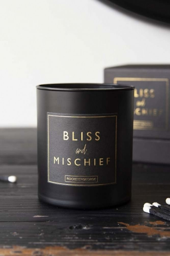 lifestyle image of Rockett St George Scented Candles - Bliss And Mischief on black wooden table with cotton buds