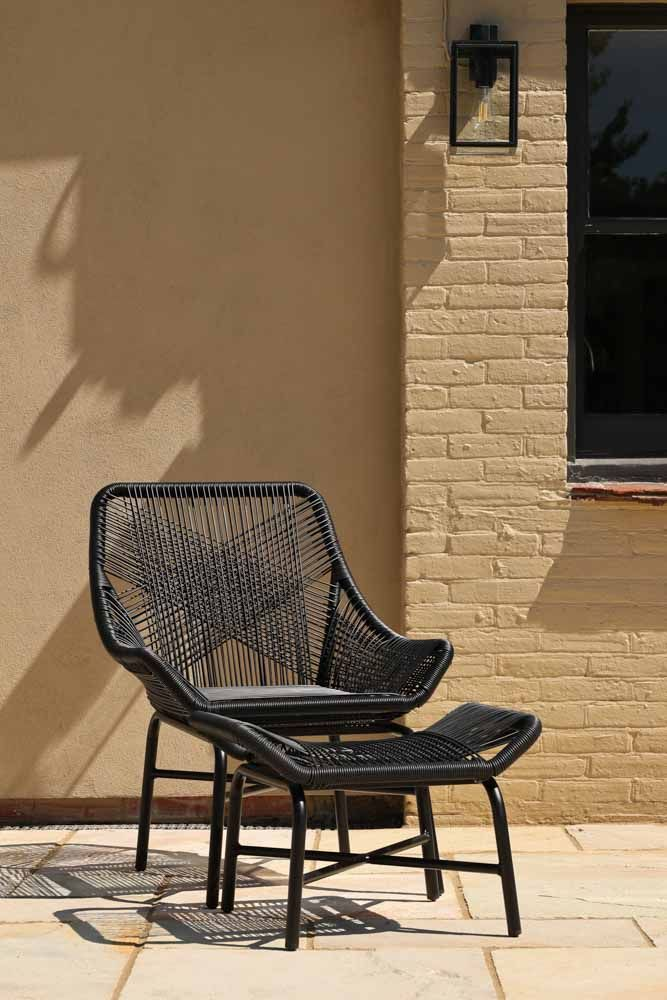 Lifestyle Image of the Alfresco Woven Rattan Outdoor Chair With Foot Stool