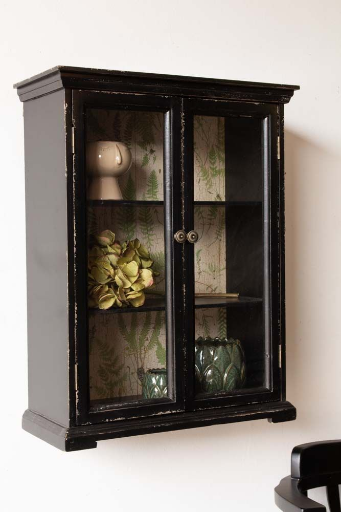 Distressed black wall cabinet on a white wall- Rockett St George filled with quirky pot and faux hydrangea plant