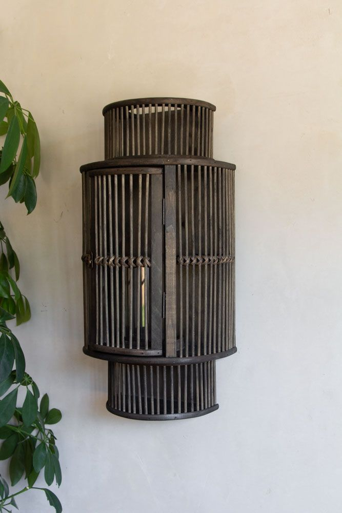 Lifestyle image of the Bamboo Curved Wall Lantern on a plaster wall with a plant to the side