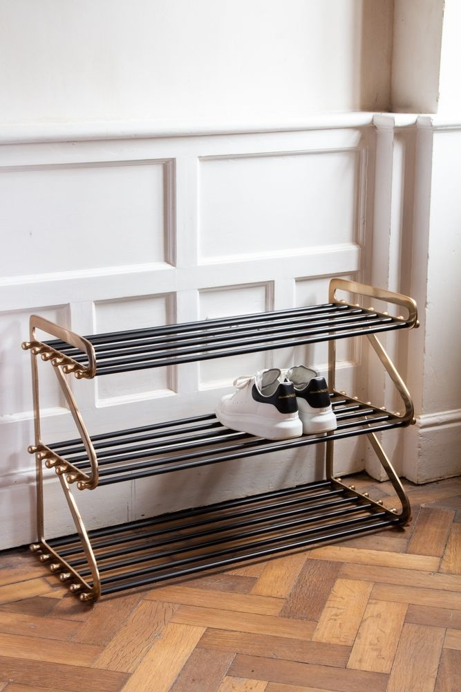 Image of the Three Tier Black & Brass Shoe Rack with a pair of trainers on it