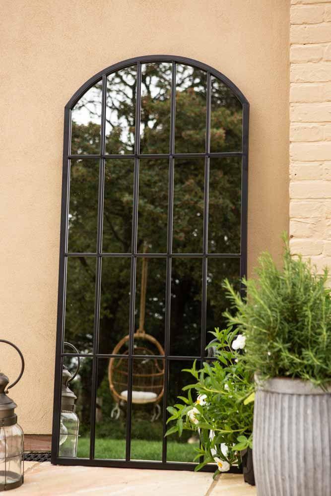 Lifestyle image of the Black Metal Window Pane Arch Indoor/Outdoor Mirror
