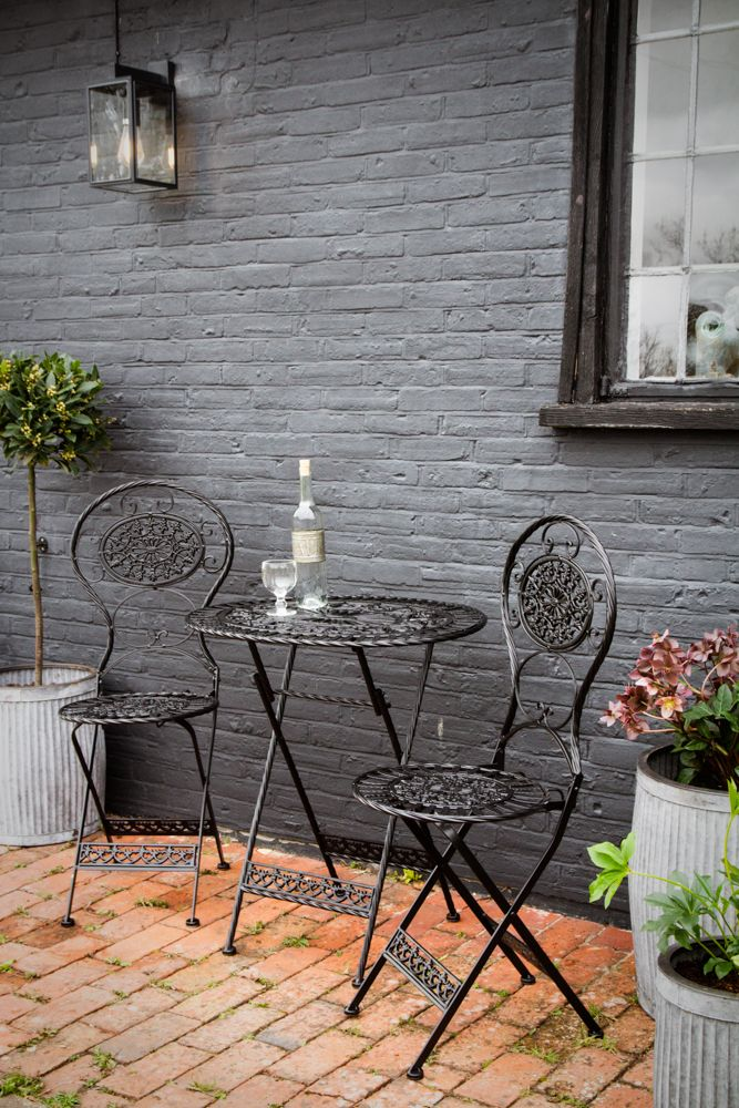 Lifestyle image of the Black Metal Garden Table & Chairs Set