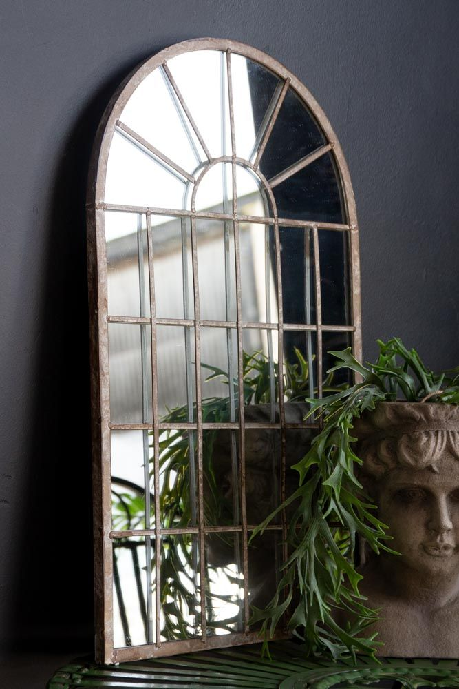 Lifestyle image of the Distressed Arch Indoor/Outdoor Mirror indoors