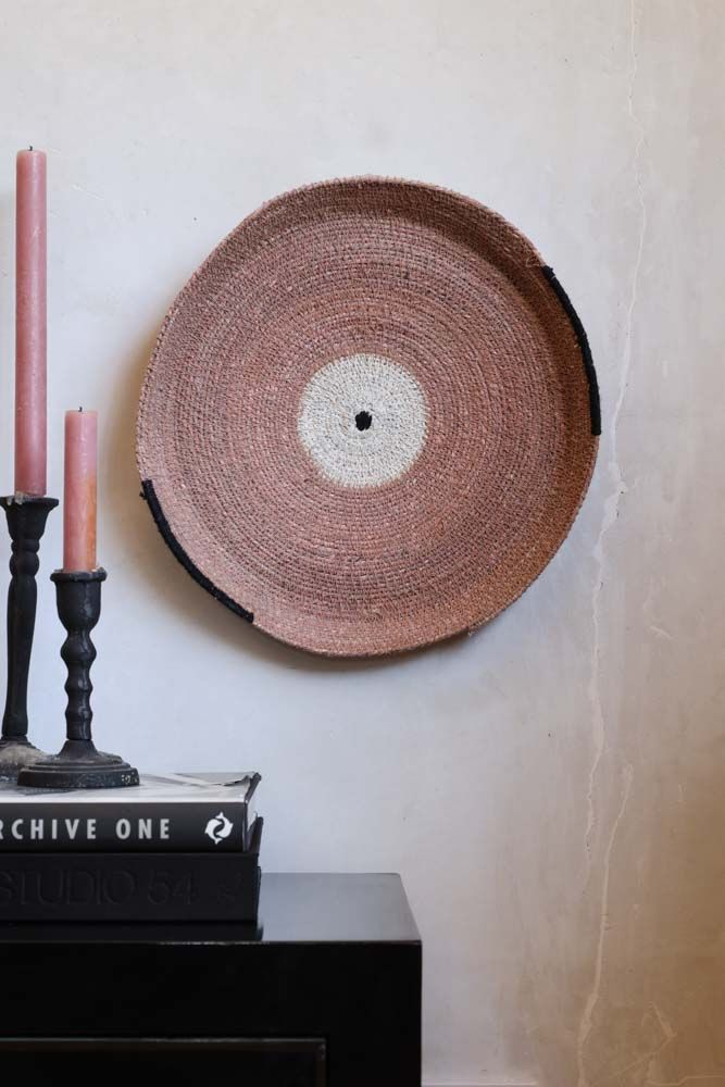 Lifestyle image of the Dusty Pink Seagrass Decorative Plate hung on a light wall