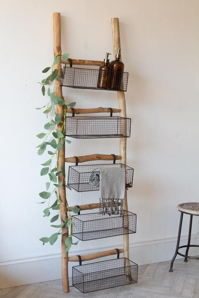 Lifestyle image of the Wooden Ladder With 5 Basket Shelves with green vine leaves wrapped around the ladder and the baskets filled with soap bottles and towels.