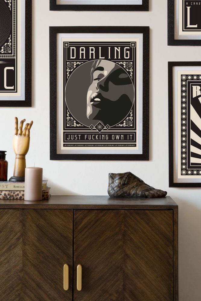 Lifestyle image of the Framed Darling Just Fucking Own It Art Print hanging on a wall