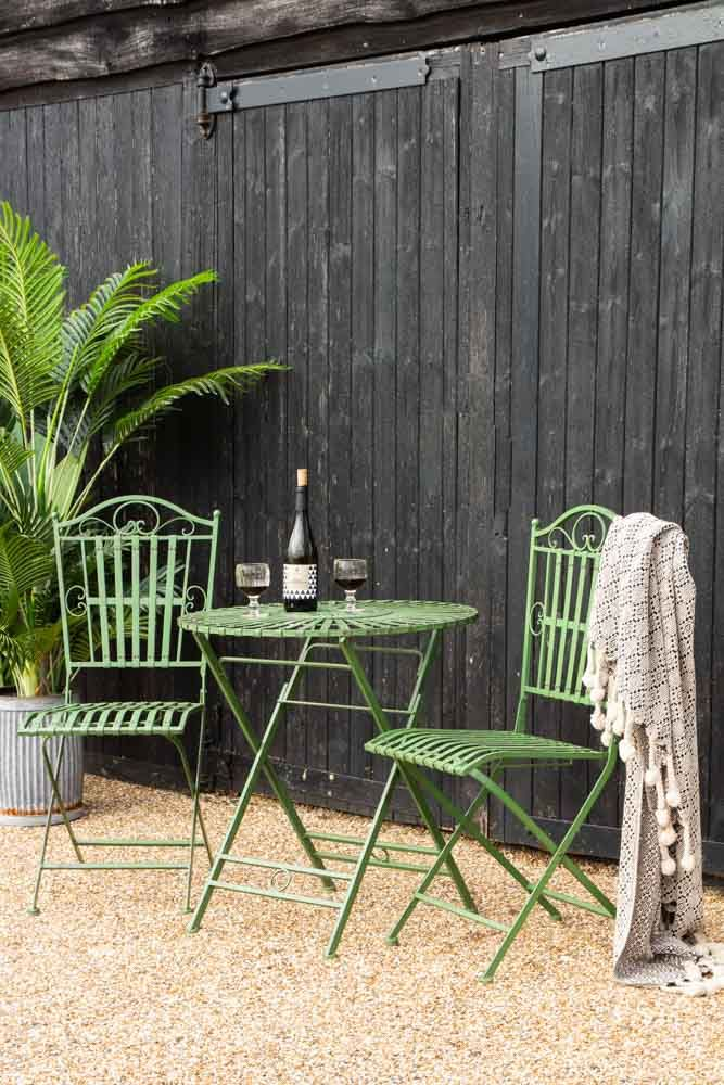 Lifestyle image of the Green Metal Garden Table & Chair Set in a garden with throw