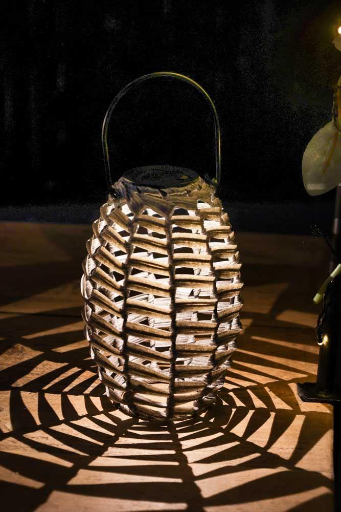 Image of the Grey Rattan Solar Lantern lit up on the floor