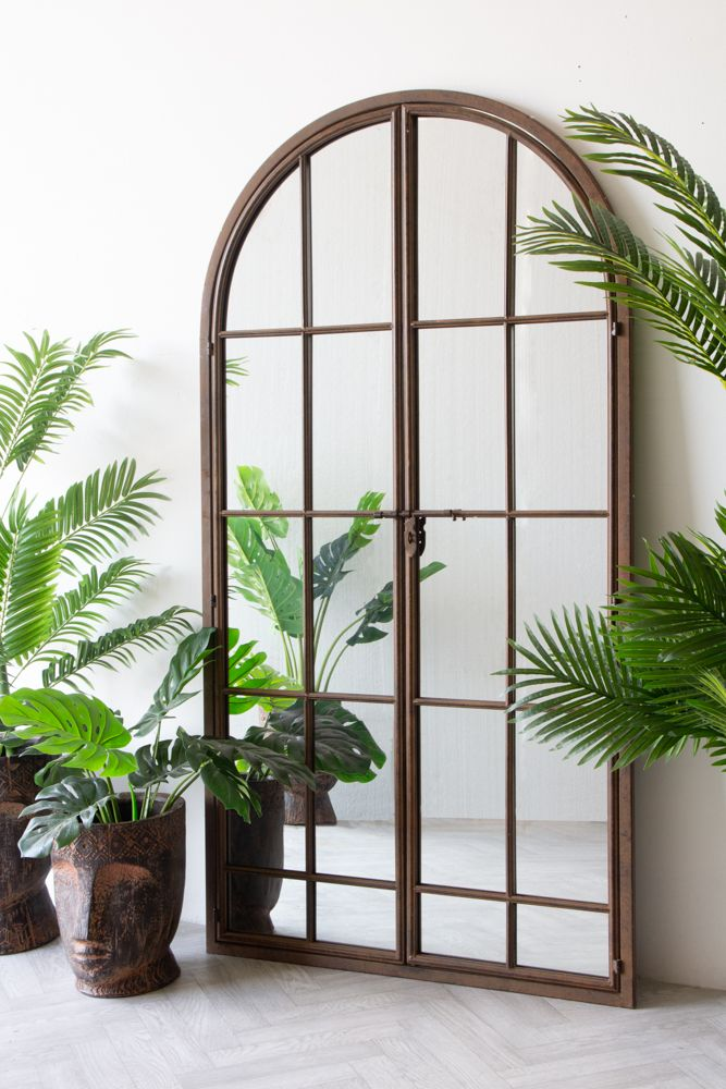 Lifestyle image of the Large Antique Metal Window Mirror With Opening Doors with the doors closed