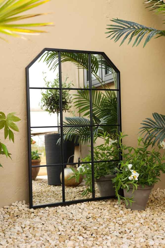 Lifestyle image of the Matt Black Window Pane Metal Indoor/Outdoor Mirror With Sloping Corners