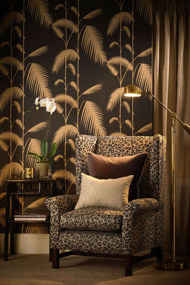 lifestyle image of cole & son new contemporary - palm leaves wallpaper - black & gold with leopard print armchair and gold floor lamp