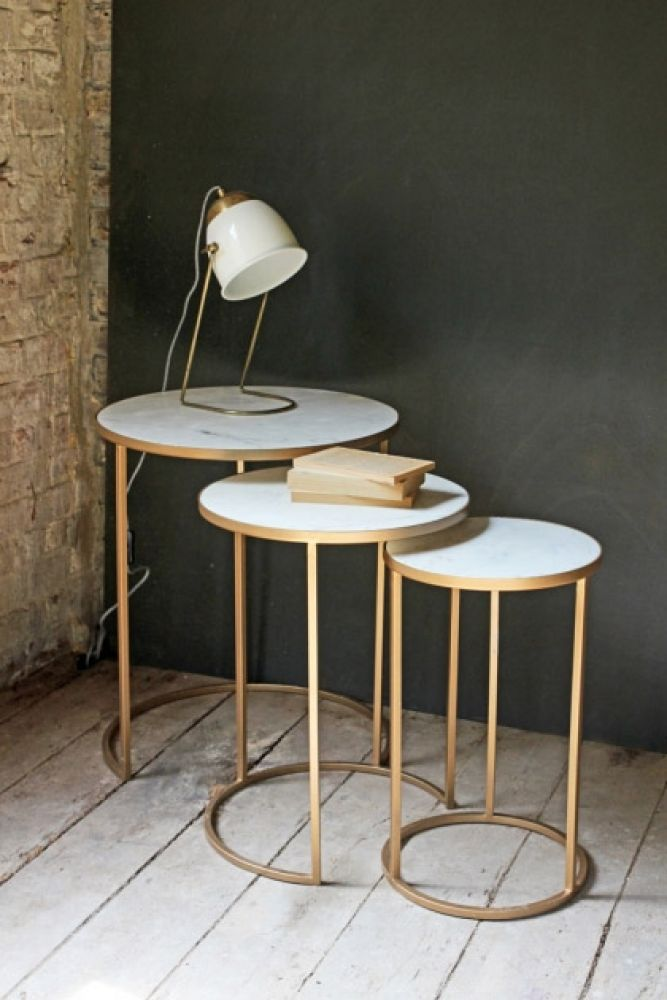 round nest of 3 marble side tables on white wooden floor and dark green background table lamp and book lifestyle image