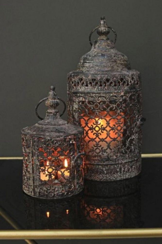 set of 2 moorish lanterns on dusky green background and lanterns lit lifestyle image
