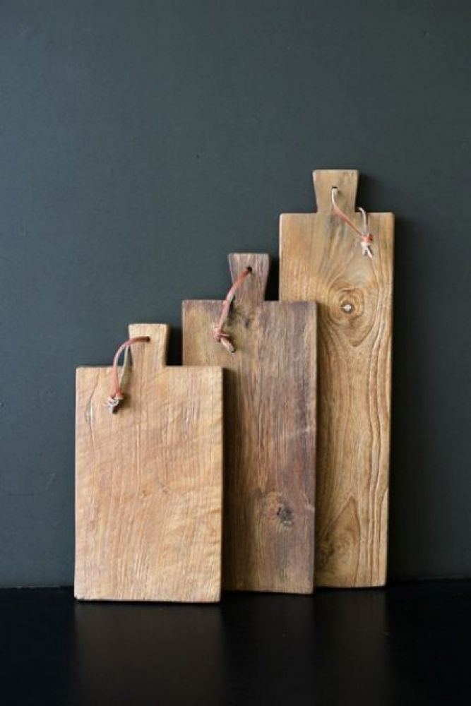 lifestyle image of set of 3 teak paddle breadboards with other wooden boards on black table with dark wall background