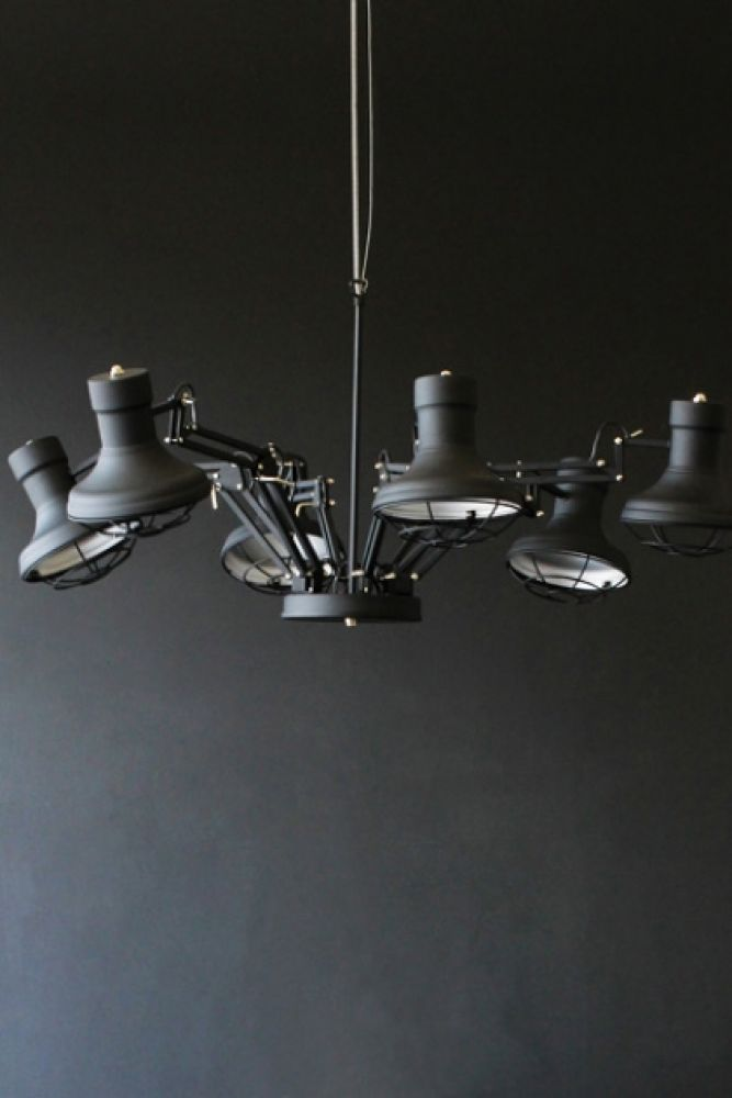 lifestyle image of six arm ceiling light with dark wall background