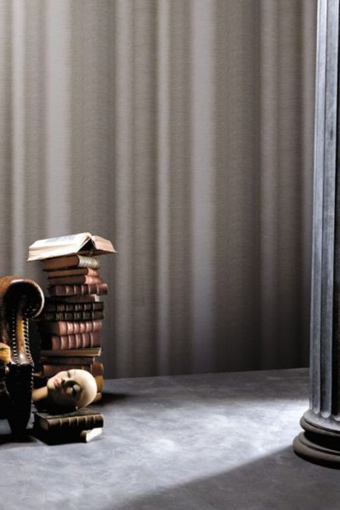 lifestyle image of koziel smoke curtain wallpaper with brown leather armchair and pile of books