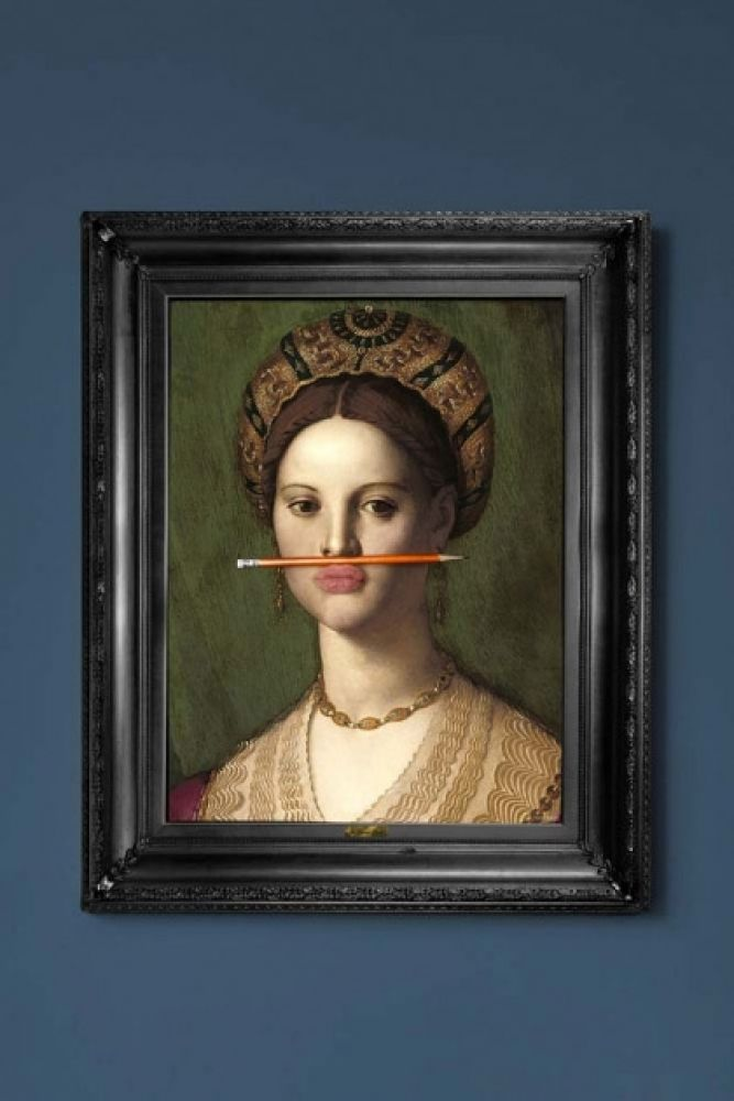 lifestyle image of the orange pencil canvas with printed frame coloured portrait with orange pencil in mouth and black frame on blue wall background