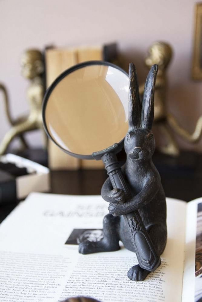 lifestyle image of wonderland rabbit magnifying glass on open book with bookends in background
