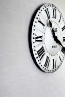 lifestyle image of Anaglypta Lincolnshire Brick Wallpaper - White with large black and white clock hanging on wall