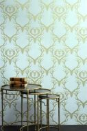 lifestyle image of barneby gates wallpaper - deer damask - duck egg blue/antique gold with nest of three tables with books on top